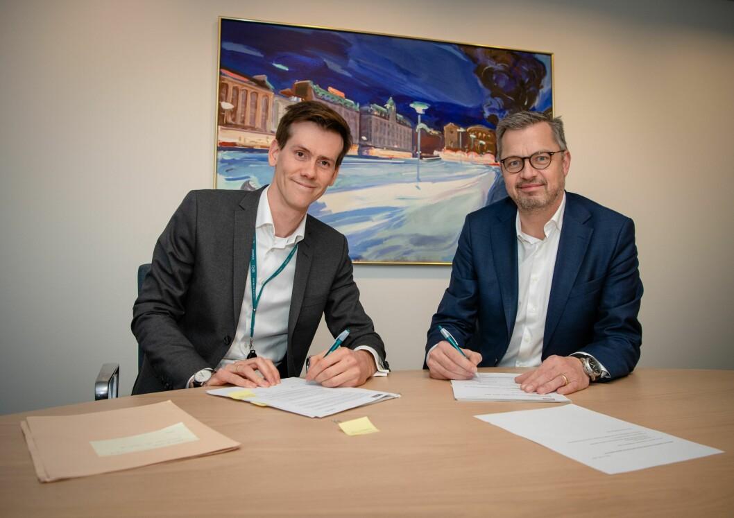Benjamin Golding fra DNB (t.v.) og Thomas Jul fra Nets signerer avtalen mellom partnerne.