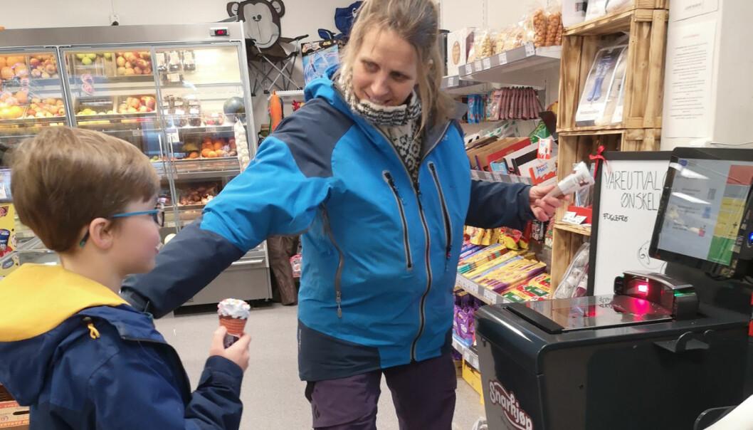 Henrik Brørvik Jordalen ser på mens bestemor Kari Brørvik selv skanner varene som er handlet. På plakaten bak ser vi at kundene kan notere vareønsker, noe som har bidratt til en kraftig utvidelse av sortimentet.
